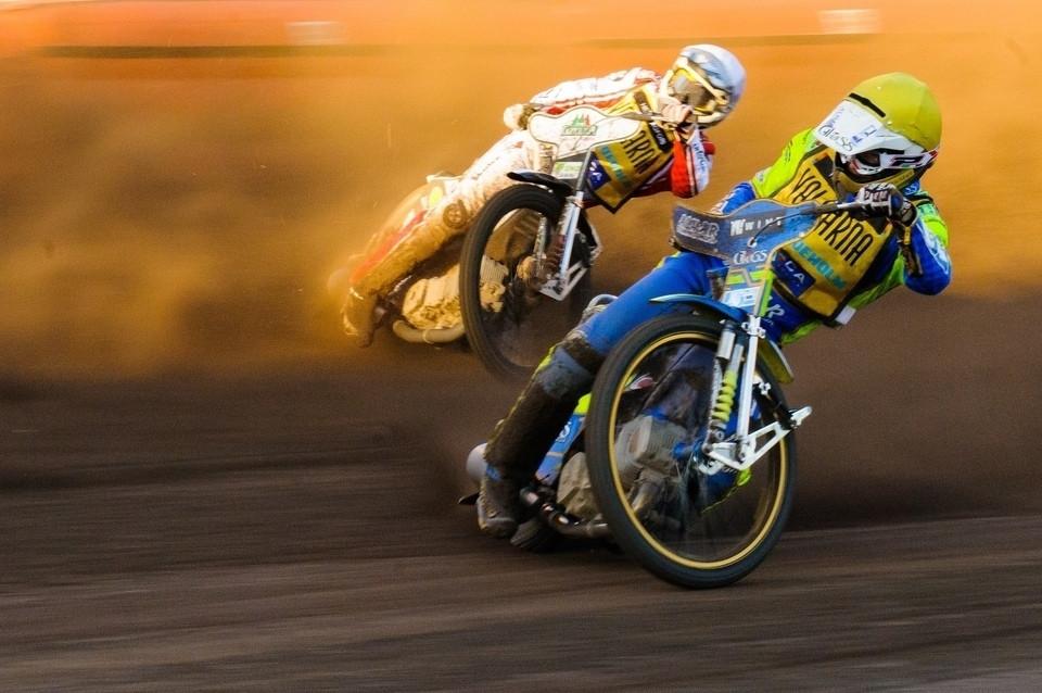שני אופנועי ספידווי בהחלקה על הצד על משטח עפר, אופנוע כחול, אופנוע לבן