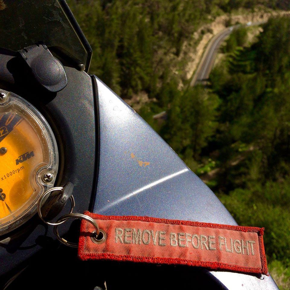 """לוח שעונים של קטמ עם מחזיק מפתחות שעליו רשום """"remove before flight"""", ברקע כביש מתפתל בין עצים"""