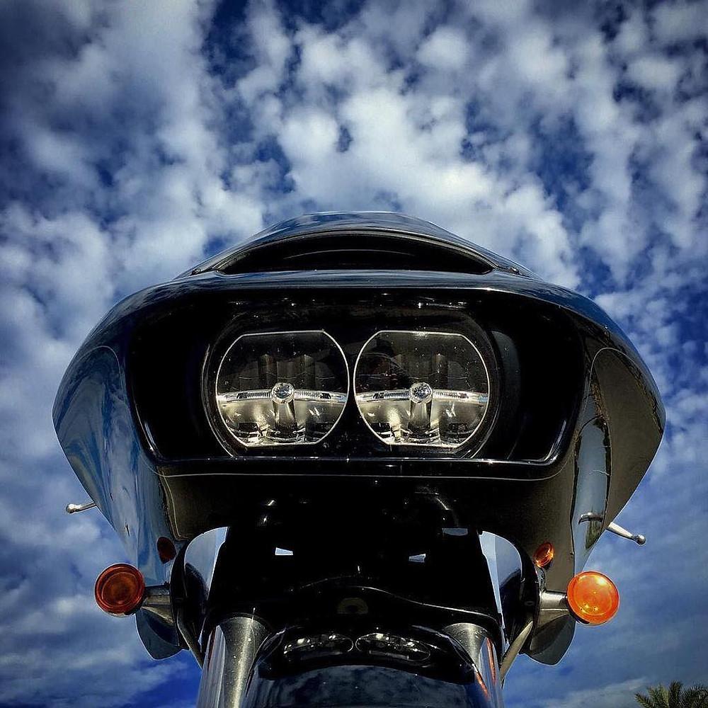מסכת חזית ופנסים של אופנוע מצולמים מלמטה ברקע שמיים כחולים ועננים