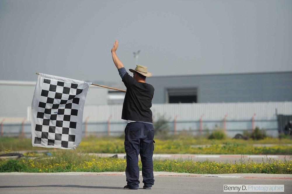 מדריך רכיבה עמסמן עם דגל שחמט סוף אימון, ברקע גדר מתכת ומבנה תעשייתי