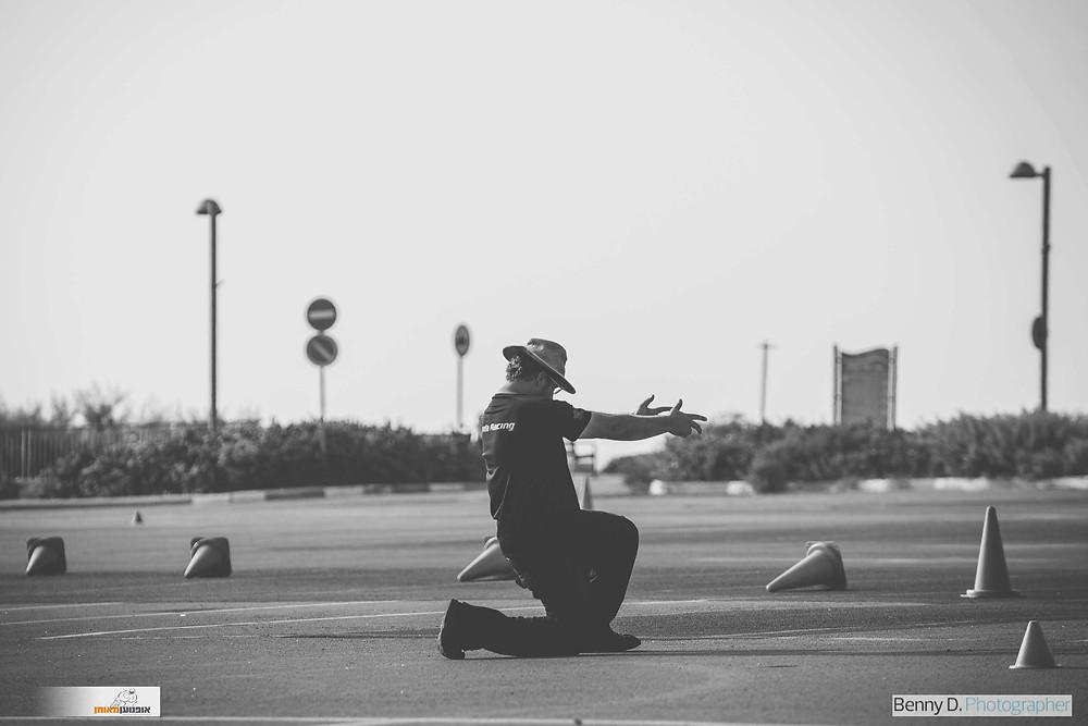 אדם כורע ברך ומושיט ידיים קדימה על מגרש עם קונוסים מפוזרים, לוגו אופנוען מאומן, לוגו בני דויטש