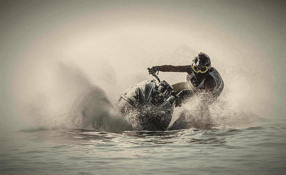 תמונה פרונטלית שחור לבן של אופנוע ים משפריץ מים בפניה
