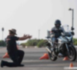 מדריך רכיבה מכוון רוכב אופנוע בין קונוסים