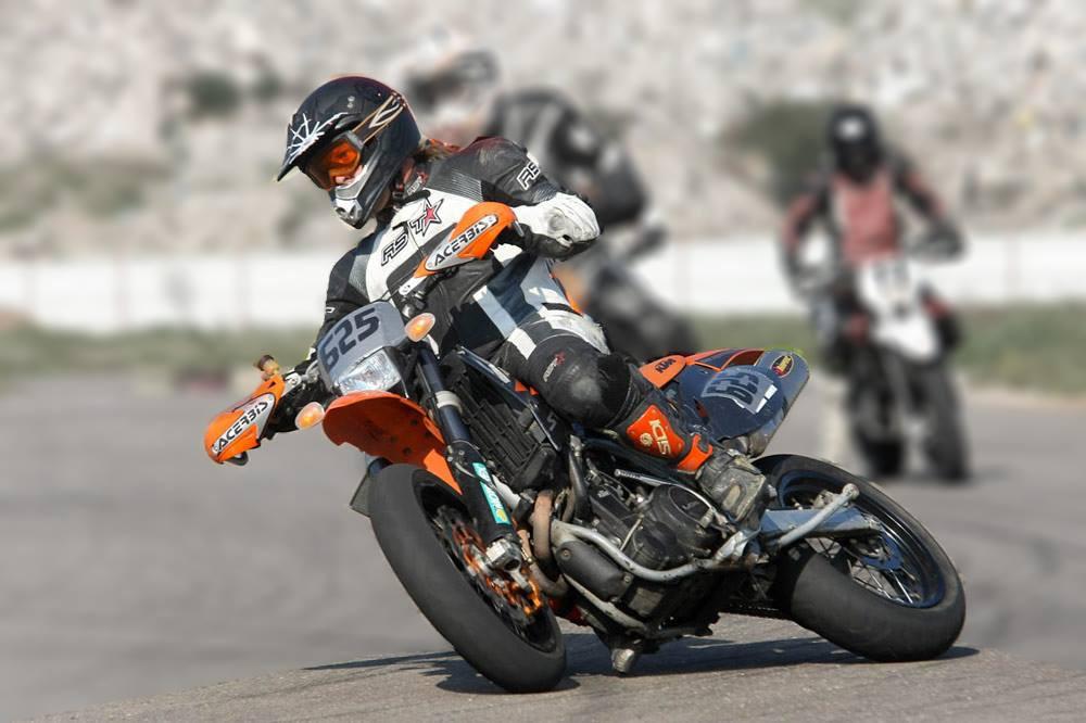 אופנוע קטמ מספר 625 בהחלקת זנב לפניה, ברקע שני רוכבים נוספים