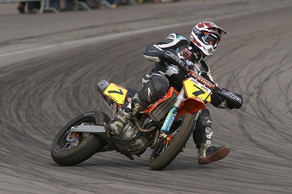 אופנוע סופרמוטו של קטמ עם לוחית מספר 7 בהחלקה של גלגל אחורי על אספלט במסלול מרוצים