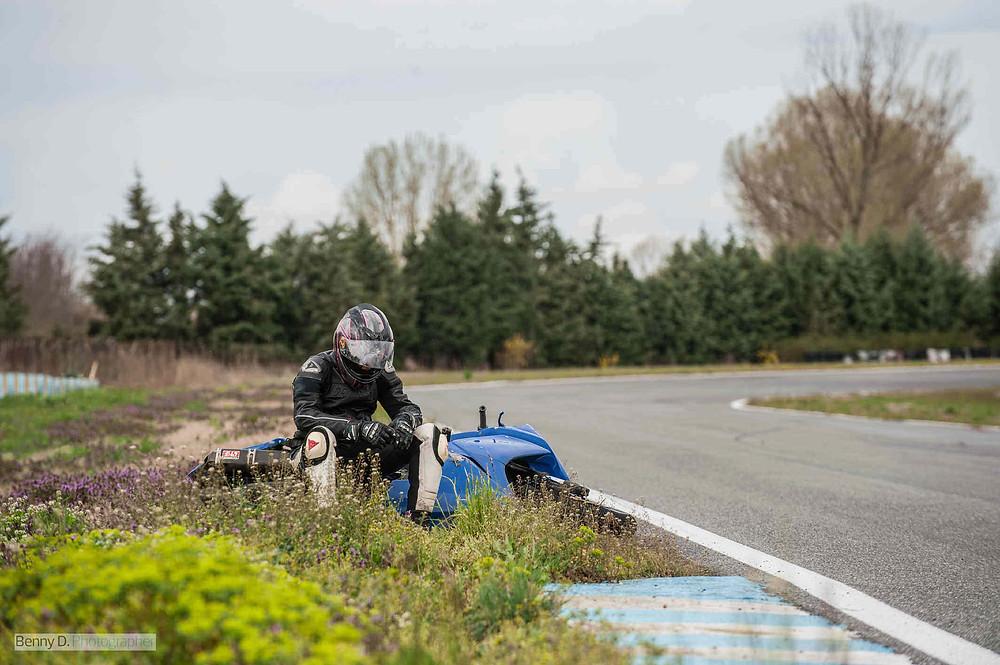רוכב יושב עם ראש מורכן על אופנוע שזרוק לצידי מסלול מירוצים אחרי נפילה, ברקע עצים ופרחים.