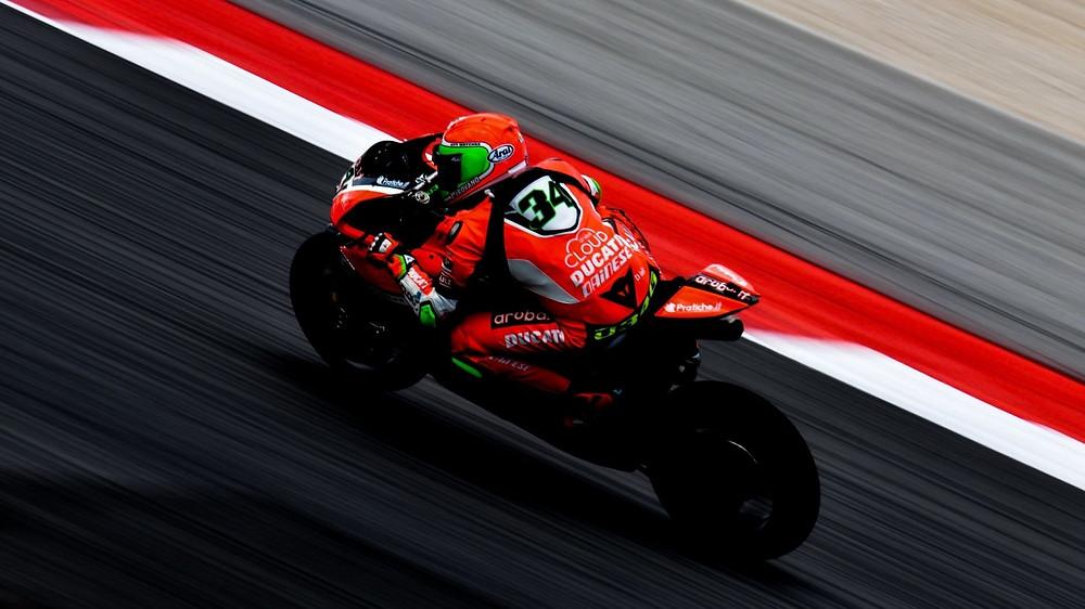 רוכב בחליפת עור אדומה על אופנוע אדום בתמונה מלמעלה על מסלול מירוצים עם שוליים צבועים באדום לבן