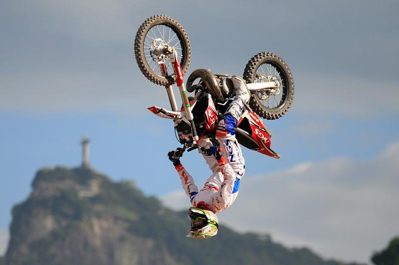 אופנוע הפוך באוויר במהלך סלטה לאחור (בק-פליפ) ברקע הר עם מגדל בפסגה