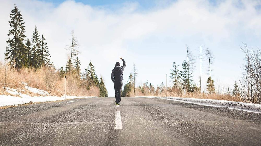 אדם עומד באמצע כביש עם הגב למצלמה ויד מונפת באוויר, בצד הכביש שלג ועצים