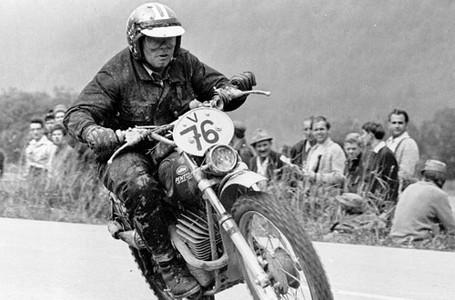 תמונה בשחור לבן של רוכב אופנוע שטח מספר 76 עם צופים ברקע