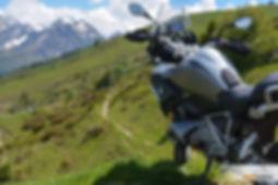 אופנוע במוו גדול על מדרון דשא עם נוף הרים