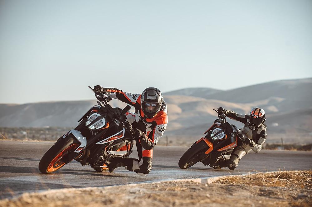 שני אופנועים, פניה במסלול, חליפות עור, הרים ברקע