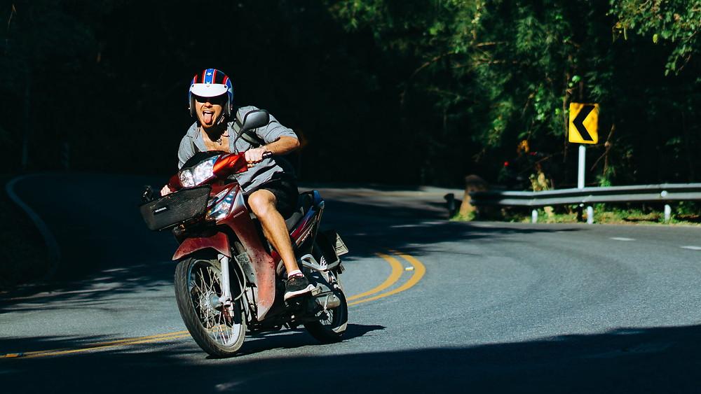 קטנוע אדום, רוכב מוציא לשון, כביש מפותל, עצים