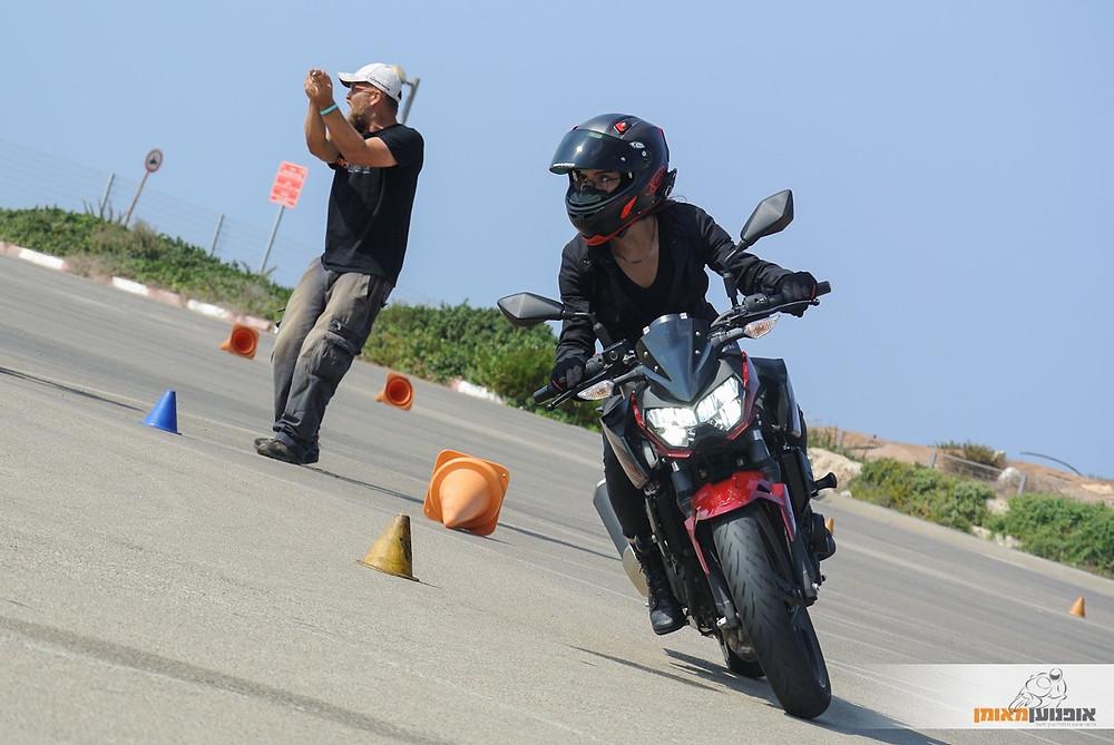 אופנוע בהטיה במגרש עם קונוסים, רוכבת עם מבט רחוק, מדריך ברקע מכוון