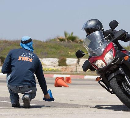 אופנוע בהטיה במגרש, מדריך רכיבה מניח קונוס במגרש, אופנוען מאומן