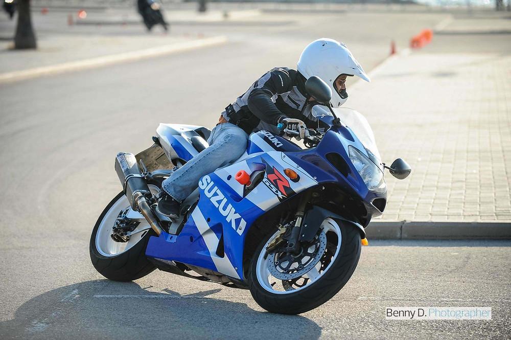 אופנוע ספורט כחול לבן בפניה, gsx1000r, רקע מגרש חניה ומדרכות