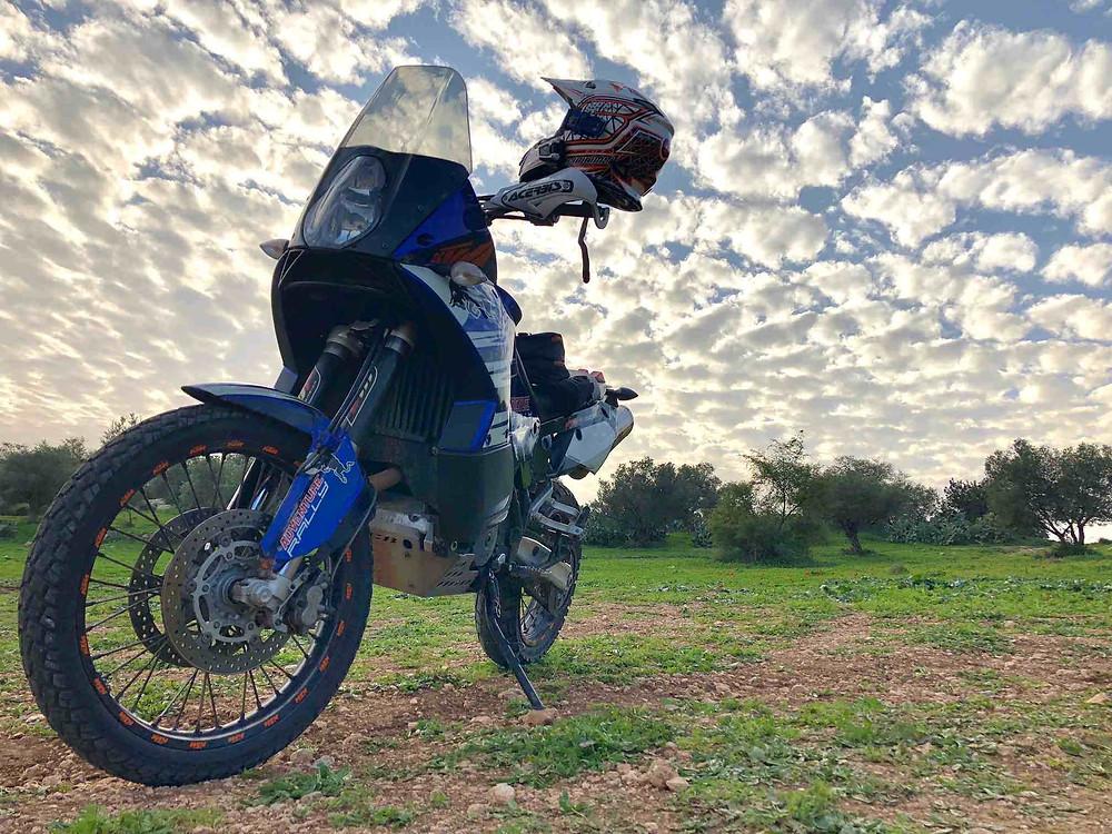 אופנוע קטמ אדווצ'ר מצולם בשטח ברקע שמיים מלאים ענני כבשה