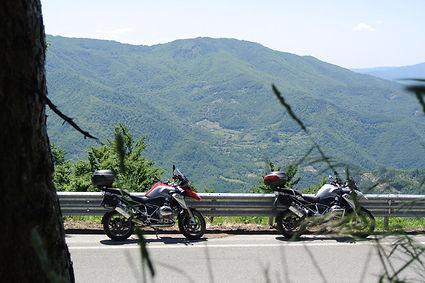 שני אופנועי תיור גדולים חונים לצד הכביש בנוף הררי