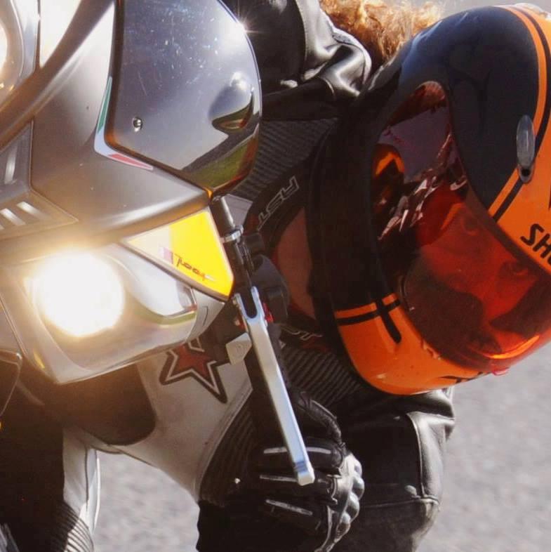 מבט מתוך קסדה כתומה. תמונת תקריב אופנוע בהטיה.