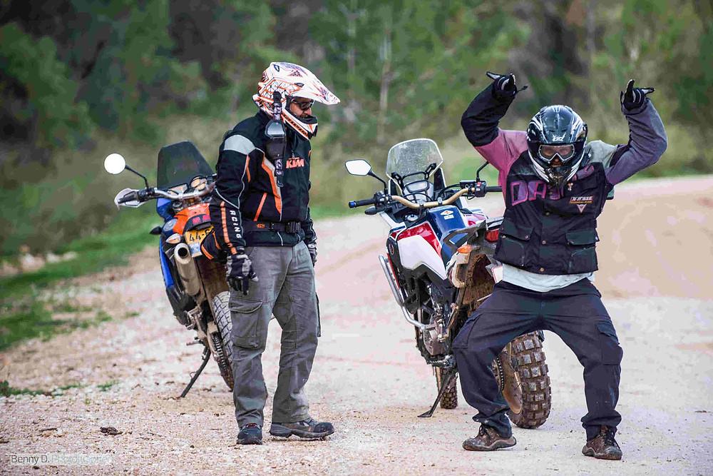 שני רוכבי אופנוע משתטים מול המצלמה וברקע אופנועי השטח שלהם על שביל כורכר ביער