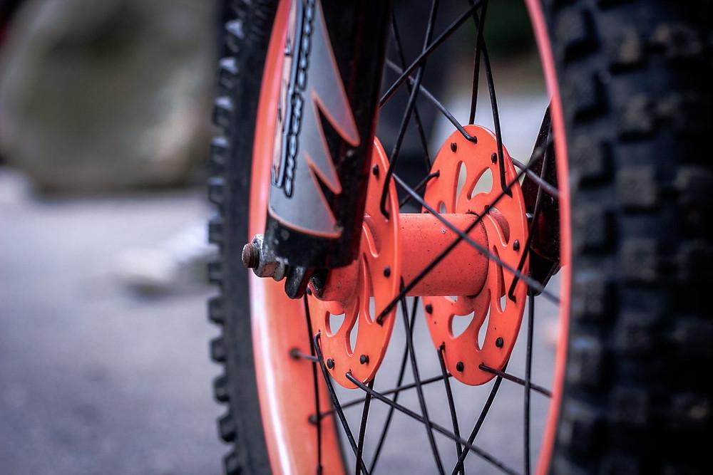 תקריב של גלגל קדמי של אופנוע עם צמיג שטח וחישוק כתום.