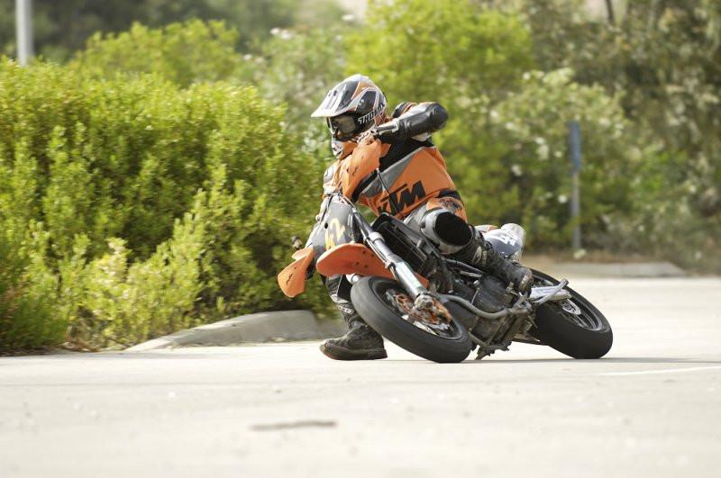 אופנוע קטמ בהשכבה קיצונית ורגל על האלספלט, רקע אספלט ושיחים