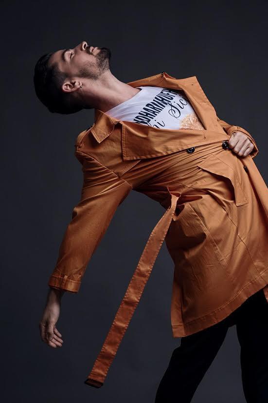 Dancer Mattia Tuzzolino in a coat performing a dance step