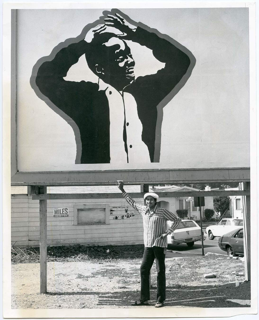 Cleveland Bellow photographed standing under his billboard of a young black boy