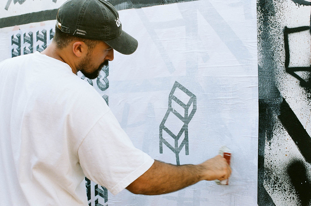 Street artist Teti painting murals on wall
