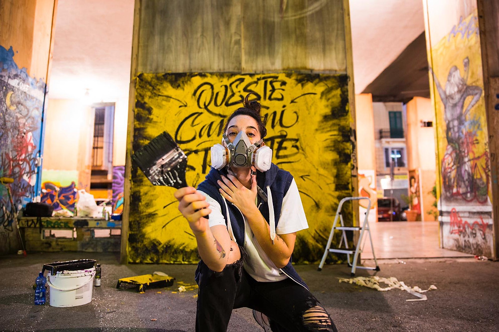 Street artist Jessica Luce Puleo with a paint brush in her hand and one of his graffiti work behind