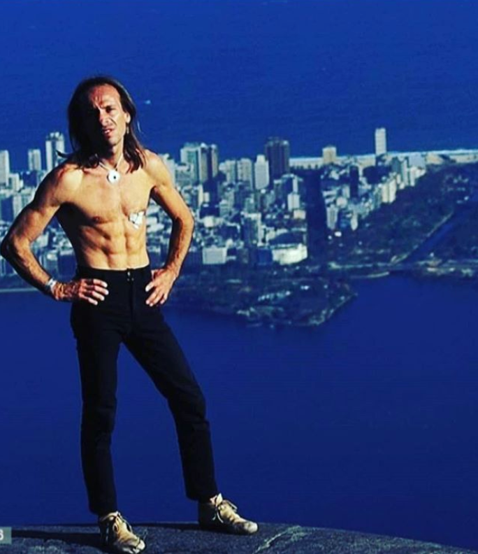 Shirtless Alain Robert and a city in the background