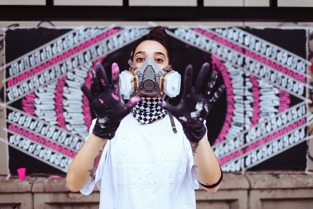 Street artist Jessica Luce Puleo with mask and her finished wall painitng behindloves and her finished