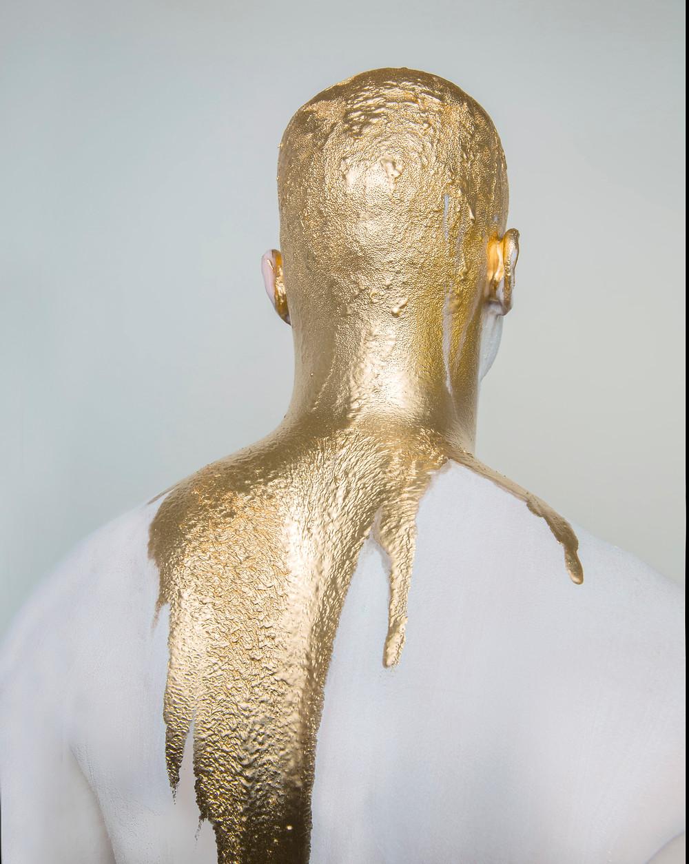 Photographer Lara Zankoul artistic shot of a man covered in liquid gold