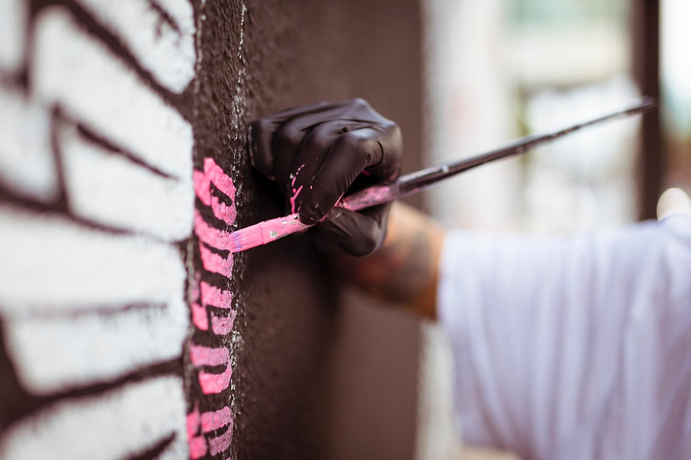 Street artist Jessica Luce Puleo working on one of her wallpaints