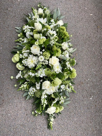 mixed supper flowers in white casket tri