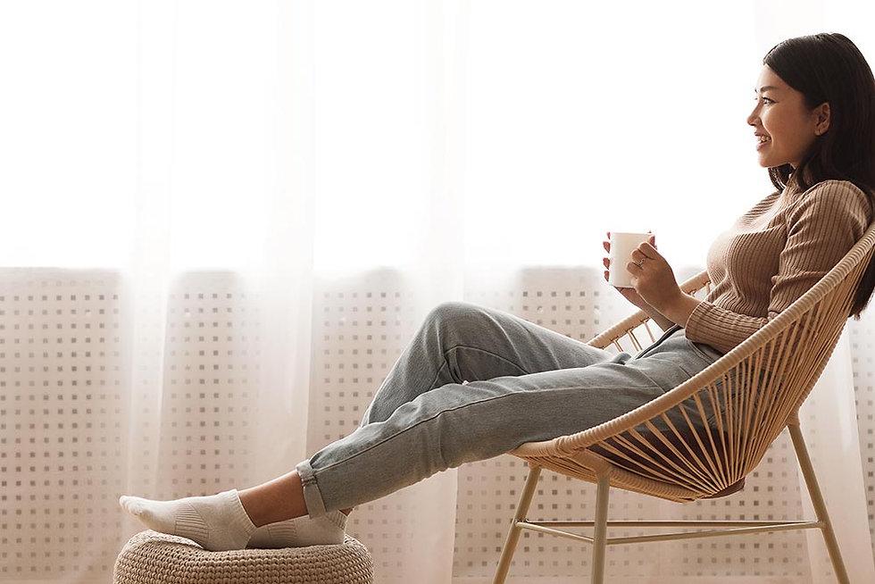 dreamy-girl-enjoying-hot-coffee-near-win