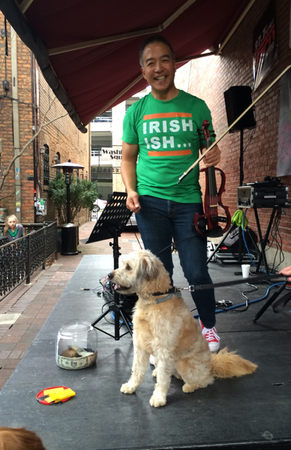 Winslow enjoys some 4-footed companionship during his St. Patrick's Day performance