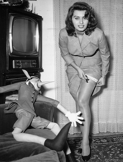 1958 Sophia Loren adjusting her stockings. The Pinocchio puppet seems to really be enjoying himself