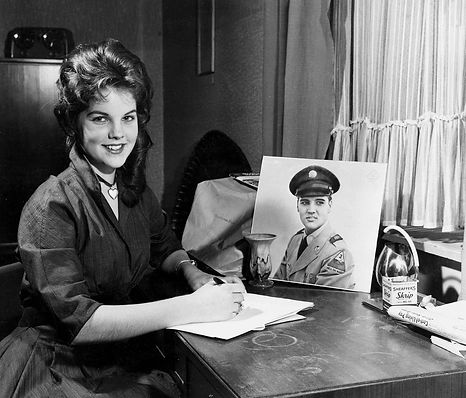 Priscilla posing for photo and pretending writing a letter to Elvis. 1960.