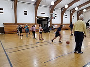 Students practicing sports in gymnasium