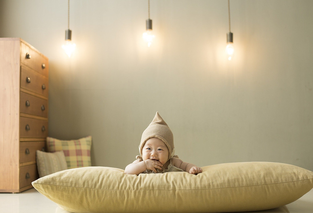 A stylish shot of an east Asian baby lying on her tummy on a big beige cushion. She has a beige pointed hat on. In the background is a chest of drawers and two small cushions.