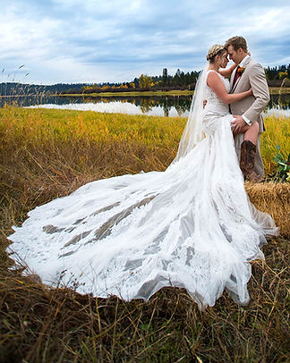 bride and groom in field next to water