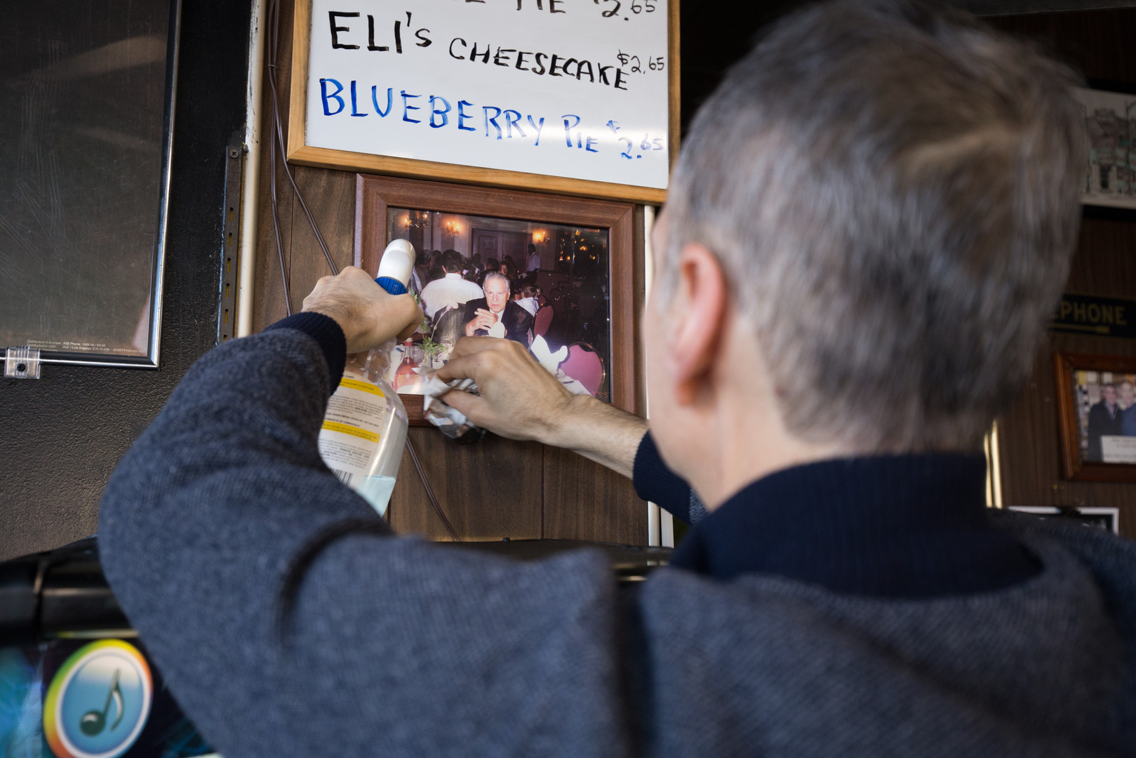 """7:42 a.m. Frank hangs a photograph of his father and original owner of Jeri's Grill, Anice, above the new jukebox. """"There's the legacy of my dad, I wouldn't be here without him—that's for sure,"""" Frank said. """"He started it all."""""""
