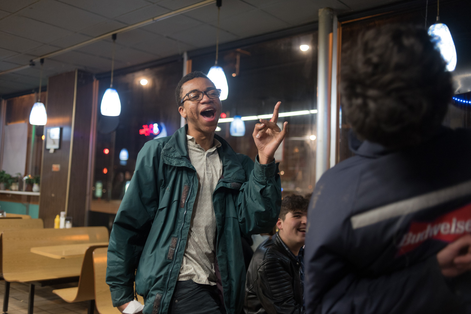 "9:58 p.m. Jabriel Martin, 18-year-old senior at Lane Technical College Prepatory High School and trumpet player for the band CASE, sings along to ""I Say a Little Prayer"" by Aretha Franklin as it plays on the jukebox. ""This is our band's song. Every time after a show in the car, this is the song we play,"" Jabriel said."