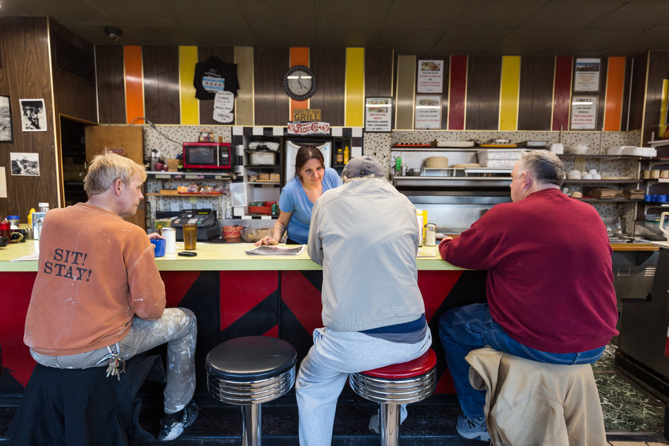 """5:24 p.m. Candice chats with three regulars (from left) William, Terry O'Neill and Howard Russell. """"If you're alone and you sit in a booth, you're in a booth,"""" Frank said. """"But at the counter, you're open to what's going on and talk to people."""""""