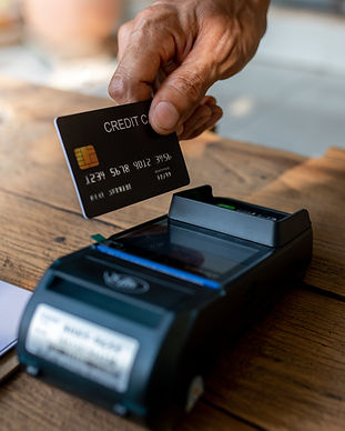 Hands of cafe visitor holding credit card and putting it to the card payment machine,moder