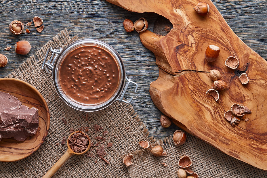 Glass jar of hazelnut spread on wooden b