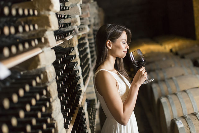 Lady sipping wine in he wine cellar
