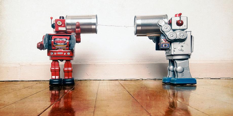 tow retro robots talk on tin can phones