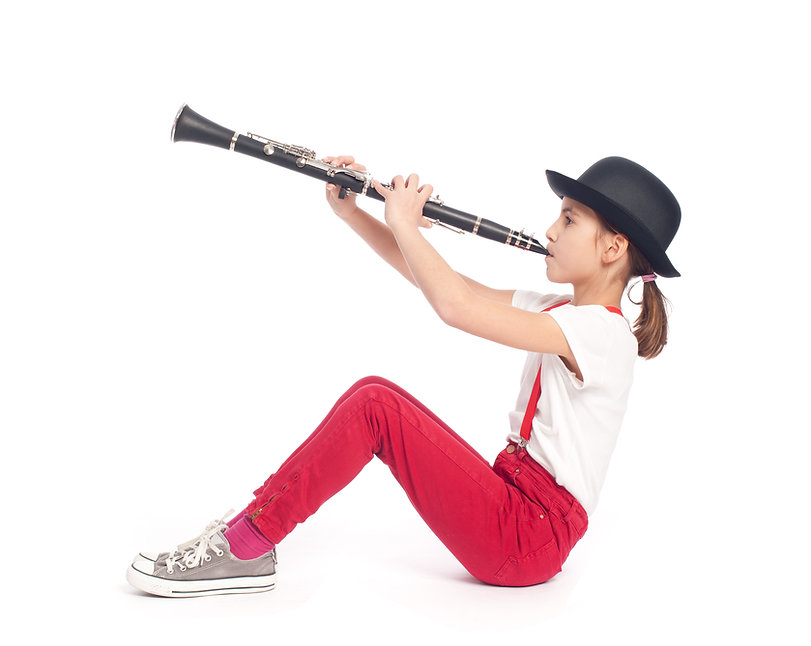 little girl playing clarinet on a white